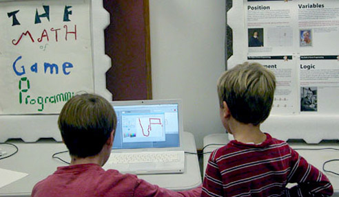 Two kids programming a game