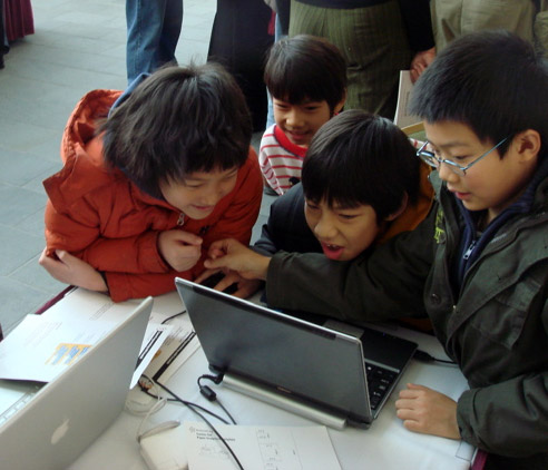 Group of excited kids focusing on a game that one of them created in the 2009 Math Camp